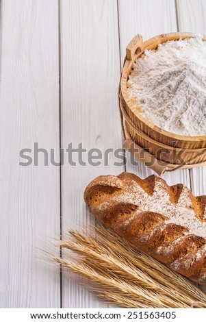 loaf of bread wheat ears flour in wooden bucket on old white boards with copyspace  - stock photo