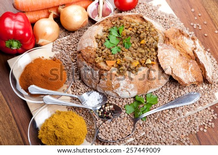 loaf of bread with lentil soup inside on wooden plate, with vegetables, indian curry spice - stock photo