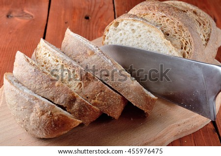 Loaf of bread with sliced pieces on a cutting board and knife, close-up. Home hle, rural style.