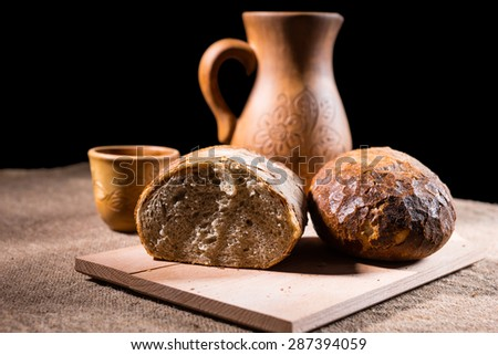 Loaf of Fresh Baked Artisinal Whole Wheat Bread Split in Half on Wooden Cutting Board on Table with Handcrafted Carved Wooden Pitcher and Drinking Cup in Background - stock photo