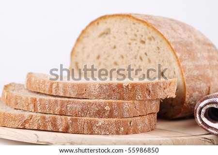 Loaf of fresh bread on cutting board - stock photo