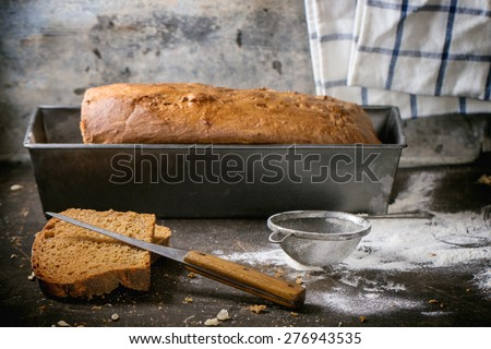 Loaf of fresh homemade rye bread with wheat seeds and flour over dark table. - stock photo