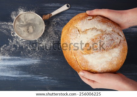 Loaf of freshly bread in female hands on color wooden table background - stock photo