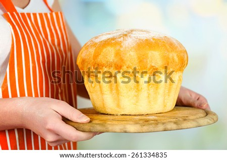 Loaf of freshly bread in female hands on wooden cutting board on light blurred background - stock photo