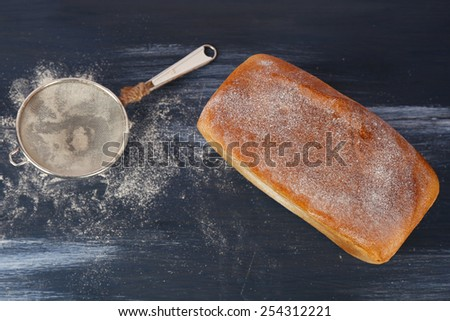Loaf of freshly bread with strainer of flour on color wooden table background - stock photo