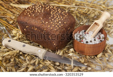 Loaf of homemade bread with black mustard seeds on a table with spikelets of rye and oat sand salt shaker salt and knife. - stock photo