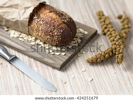 Loaf of rustic whole grain bread in paper bag on wooden board with knife, millet spray, and loose grains. - stock photo