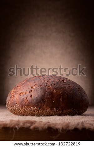 Loaf of rye bread on rustic background - stock photo