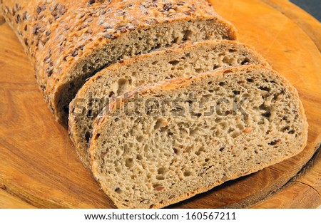 loaf of sliced bread at a wooden board - stock photo