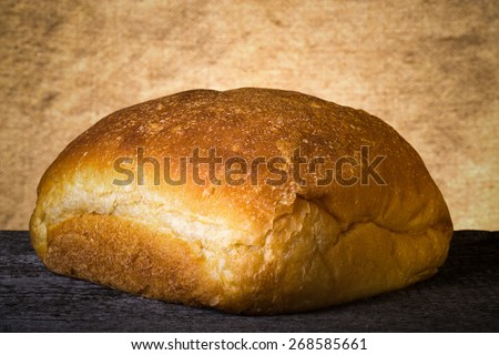 Loaf of white wheat bread on old wooden table. Toned. - stock photo