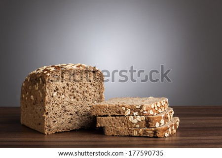 Loaf of wholemeal bread and slices on table in front of gray background. - stock photo