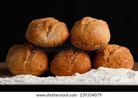 loaves of bread on black background - stock photo