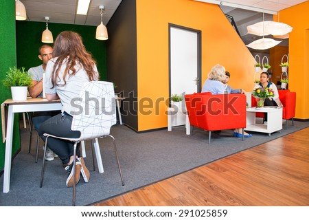 Lobby and multi-purpose waiting area, with several groups of people sitting at tables during informal meetings of a modern styled office - stock photo