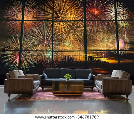 Lobby area of a hotel which can see Fantastic festive new years colorful fireworks on the evening sky with majestic clouds - stock photo
