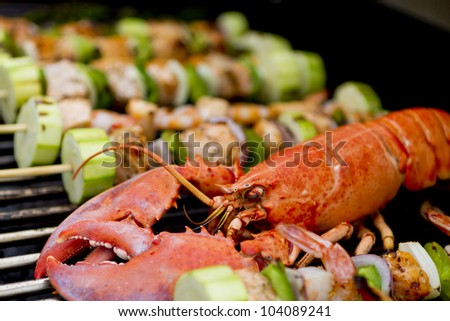 Lobster and fish skewers are on the barbecue. - stock photo