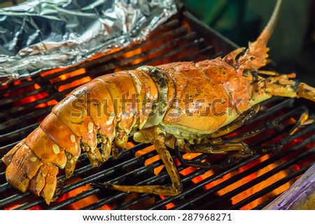 lobster dinner at the restaurant seafood by fire and BBQ Flames. - stock photo