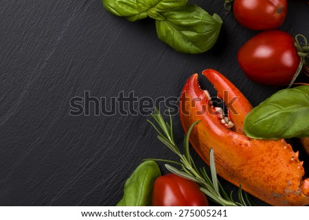 Lobster leg on blackbackground with herbs and tomatoes - stock photo