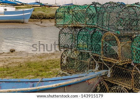Lobster pots with boats on a sea inlet - stock photo