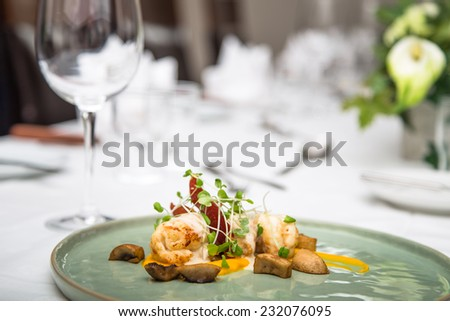 Lobster tail appetizer on a plate at a set table in restaurant - stock photo
