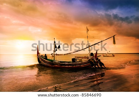 local boat on the beach at sunset time . Bali , Indonesia - stock photo