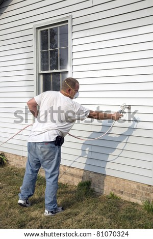 Local contractor painting outside of house, business is booming in summer months - stock photo
