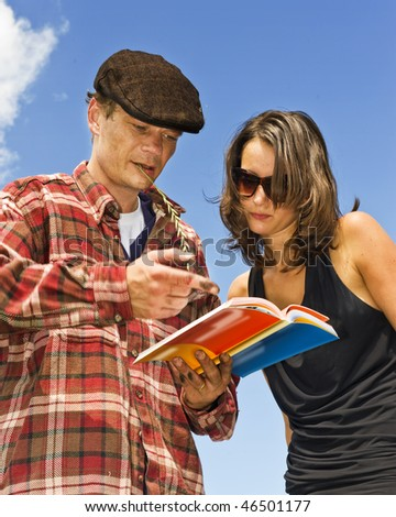Local farmer acting as a temporary tour guide, explaining the sights to a smartly dressed beautiful young woman - stock photo