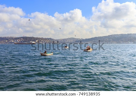 Local fisherman boats in the Bosphorus strait, Istanbul, Turkey. The Bosphorus or Bosporus is a narrow, natural strait connects the Black Sea with the Sea of Marmara.