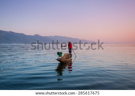 Local fishermen are fishing by boat in unique style, Inle lake, Myanmar - stock photo