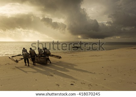 Local fishermen of Zanzibar taking a traditional boat on water with thunder clouds in background at sunset - stock photo