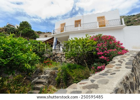 Local house lost on vegetation on Alicudi island, Aeolian Islands, Sicily, Italy. - stock photo