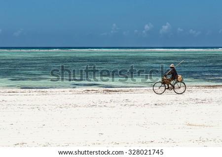 Local Riding Bike Down Beach, Zanzibar, Tanzania - stock photo