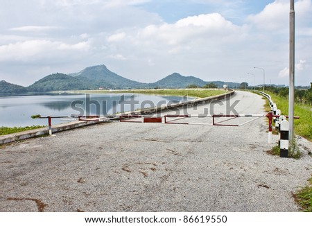 Local road beside a dam with barrier - stock photo