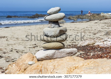 Local rock art on a sandy beach with gentle waves and surf in the background along the rugged Big Sur coastline, near Cambria, CA. on the California Central Coast. - stock photo