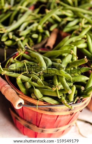 Locally grown organic green beans in colorful baskets for sale at local farmers market - stock photo