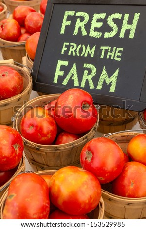Locally grown re tomatoes for sale at local farmers market with handwritten chalk board sign - stock photo