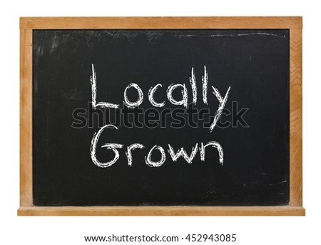 Locally grown written in white chalk on a black chalkboard isolated on white