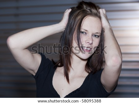 Location shoot of a beautiful young woman, wearing a black top and standing in front of a garage door and holding her hair up.