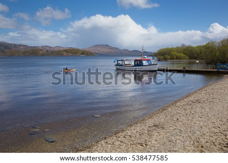 Loch Lomond Scotland UK in summer with blue sky boat and jetty popular Scottish tourist destination
