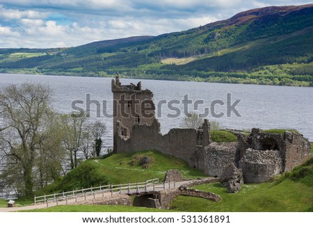 Loch Ness, Scotland - June 2, 2012: The ruins of  Urquhart Castle sit on a green cliff looking over  Loch Ness. Surrounding green hills. Light blue sky with white clouds.
