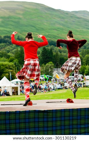 LOCHEARNHEAD, SCOTLAND- JULY, 24,2010: Two girls in traditional dress compete in the sword dance event at Highland Games on July, 24, 2010 in Lochearnhead. - stock photo
