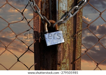 lock key with shackles on rusty fence  - stock photo