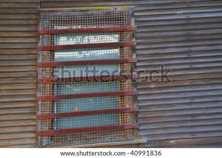 Locke barred and screened window bordered by old weatherd wood wall - stock photo