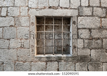 Locked ancient stone prison wall with metal window bars - stock photo