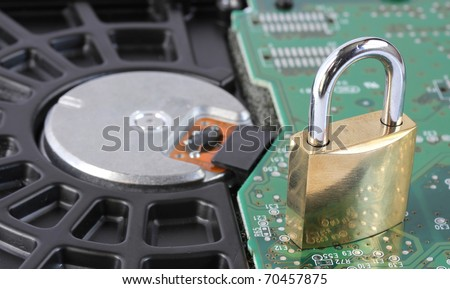 locked closed padlock sitting on a computer hard disk drive representing data security - stock photo