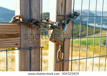 Locked gate on beautiful landscape - stock photo