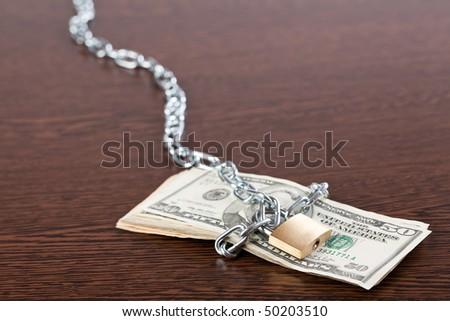 locked money on wooden table - stock photo