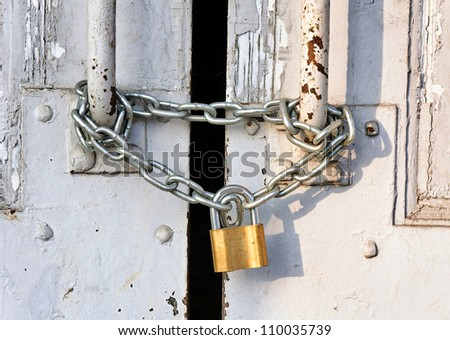 Locked old and rusty door - stock photo