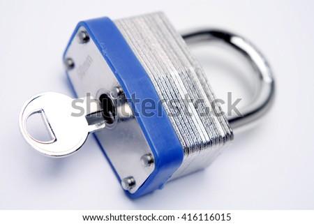 Locked padlock and key inside it - stock photo