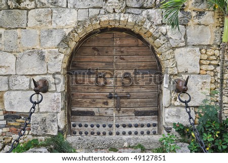 locked wooden door with round doorknobs and chains - stock photo