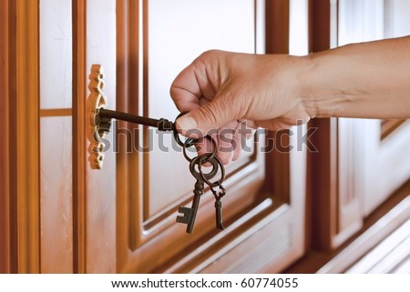 Locking up or unlocking the door with a key in hand - stock photo